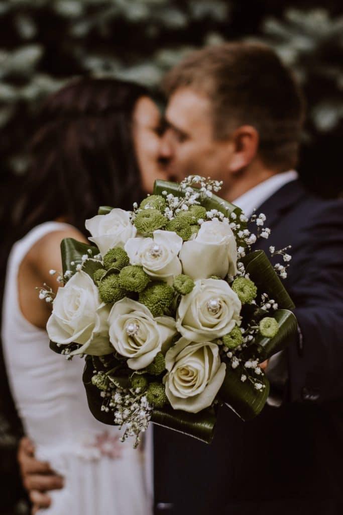 Couple s'embrasse lors de son mariage, avec un bouquet de fleurs